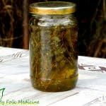 Thyme herbs with olive oil in a glass jar ready to infuse.